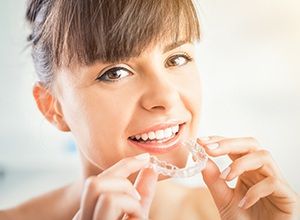 Woman placing clear Invisalign tray