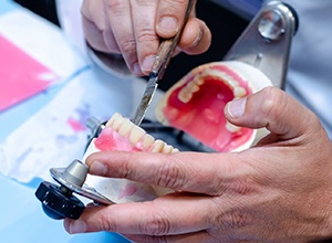 close-up of dental lab technician working on dentures