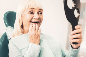 Senior woman admiring her smile after receiving partial denture