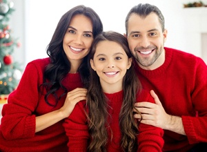 A happy family smiling and wearing red