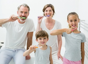 A family all brushing their teeth at home
