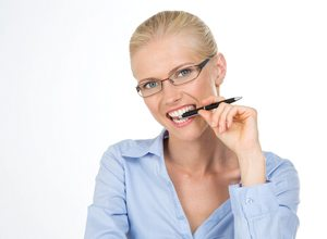A woman biting down on a pen