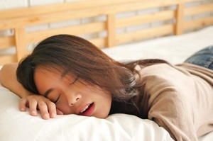 Snoring young woman with brown hair taking a nap