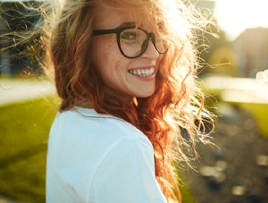 Smiling woman in glasses enjoying benefits of tooth-colored fillings