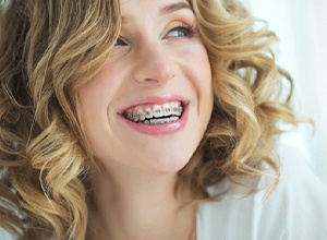 Smiling young woman with traditional braces in Newington