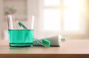 toothbrush and toothpaste next to mouthwash — dental hygiene tools
