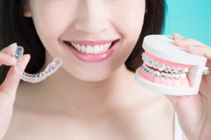 Woman holding traditional braces and Invisalign in Newington
