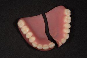 Broken full denture in Newington against black background