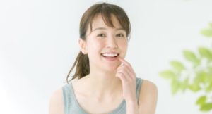 Happy woman with dental implants after tooth extraction
